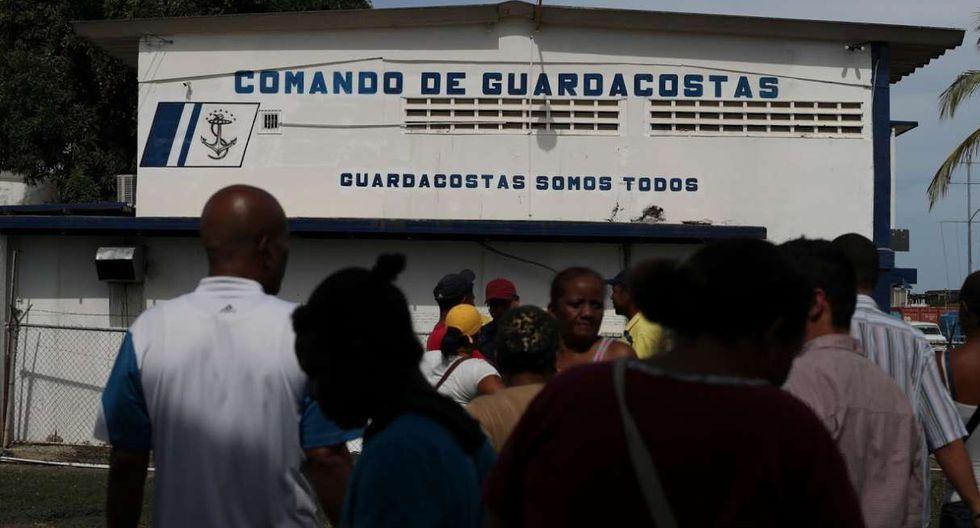 Familiares de personas que desaparecieron en el mar Caribe después de abordar un barco de traficantes durante un intento de cruzar de Venezuela a Trinidad y Tobago, se reúnen frente al edificio de la guardia costera. (Foto: Reuters)