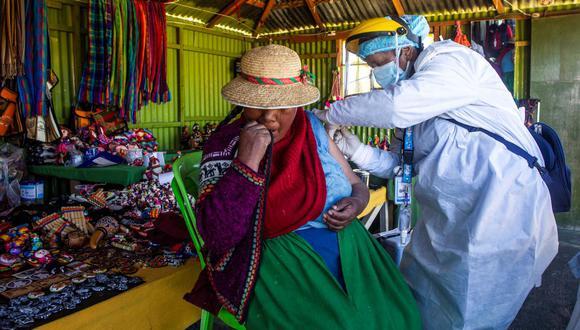 Un trabajador de la salud inocula a una mujer con una dosis de la vacuna Sinopharm contra el coronavirus COVID-19 en la isla de los Uros, en el lago Titicaca, Perú. (CARLOS MAMANI / AFP).