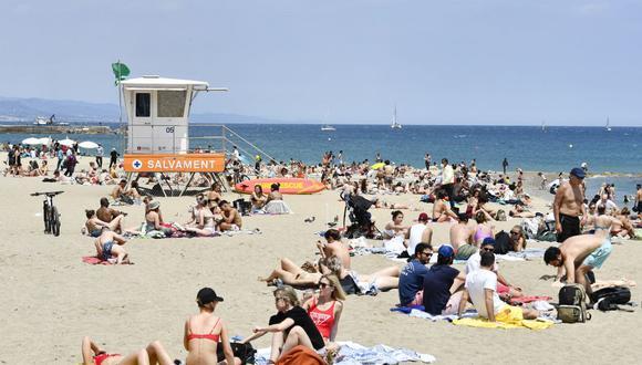 La gente toma el sol en la playa de la Barceloneta el 6 de junio de 2021 en Barcelona, España. (Foto de Pau BARRENA / AFP).