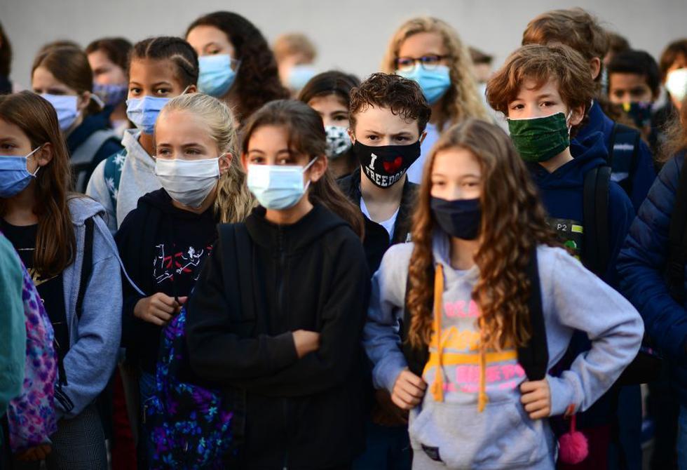 Alumnos con mascarillas protectoras escuchan a una mujer en la escuela secundaria Françoise-Giroud en Vincennes, al este de París, el 1 de septiembre de 2020, en el primer día del año escolar en medio de la pandemia de oronavirus Covid-19. (Foto de Martin BUREAU / AFP).