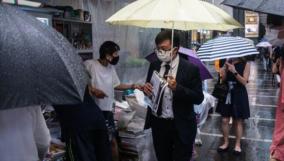 Un hombre sostiene un periódico tras hacer cola para comprarlo en un quiosco de Hong Kong. (Foto referencial, Anthony WALLACE / AFP).