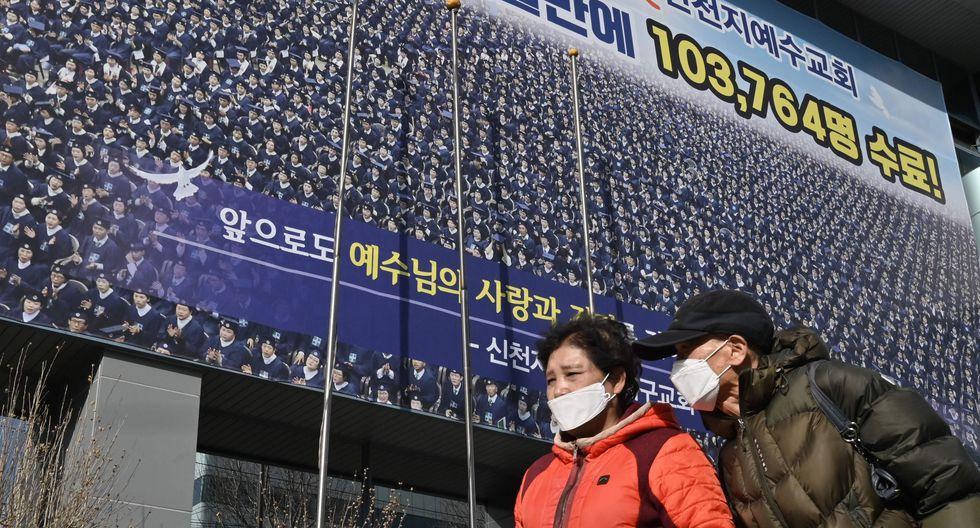 Dos personas que usan máscaras faciales pasan cerca de un templo de la secta Shincheonji en Daegu, Corea del Sur. (AFP / Jung Yeon-je).