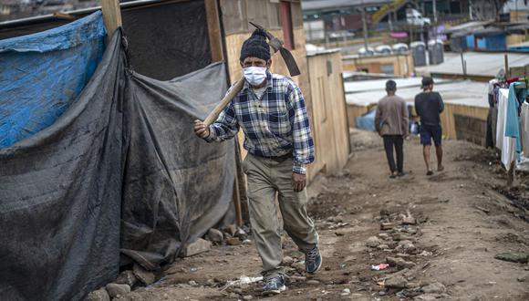 Un hombre cargando un pico camina en la comunidad de Cantagallo, cuyos habitantes esperan ser beneficiados con el segundo bono (Foto: AFP)