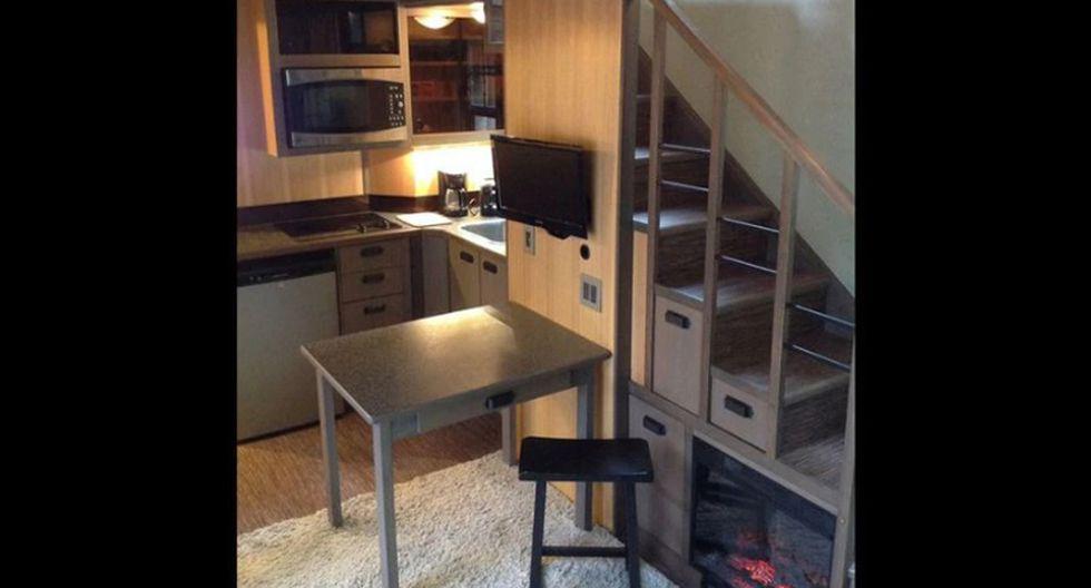 La sala de estar es acogedora, con acabados en madera y metal. El sofá se despliega para usarse cuando llegan invitados a la casa. La cocina está ubicada debajo de la escalera para así aprovechar el espacio. (Foto: tinyhouse.heininge.com)