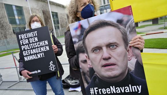 """Los manifestantes muestran un retrato del crítico del Kremlin Alexei Navalny y una pancarta que dice """"Libertad para el preso político Navalny"""" durante una protesta en su apoyo frente a la cancillería en Berlín, Alemania. (Foto de John MACDOUGALL / AFP)."""