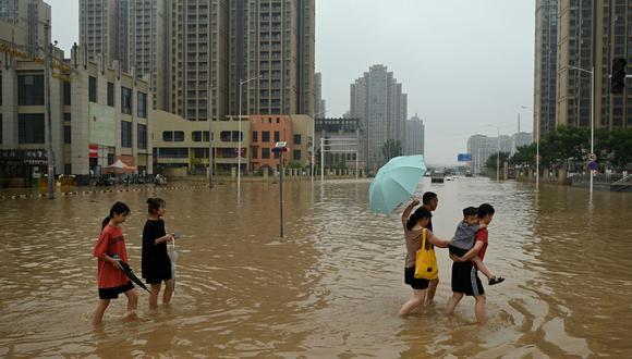 La gente cruza una calle inundada luego de las fuertes lluvias en la ciudad de Zhengzhou, en la provincia china de Henan, el 23 de julio de 2021. (Foto de Noel Celis / AFP).