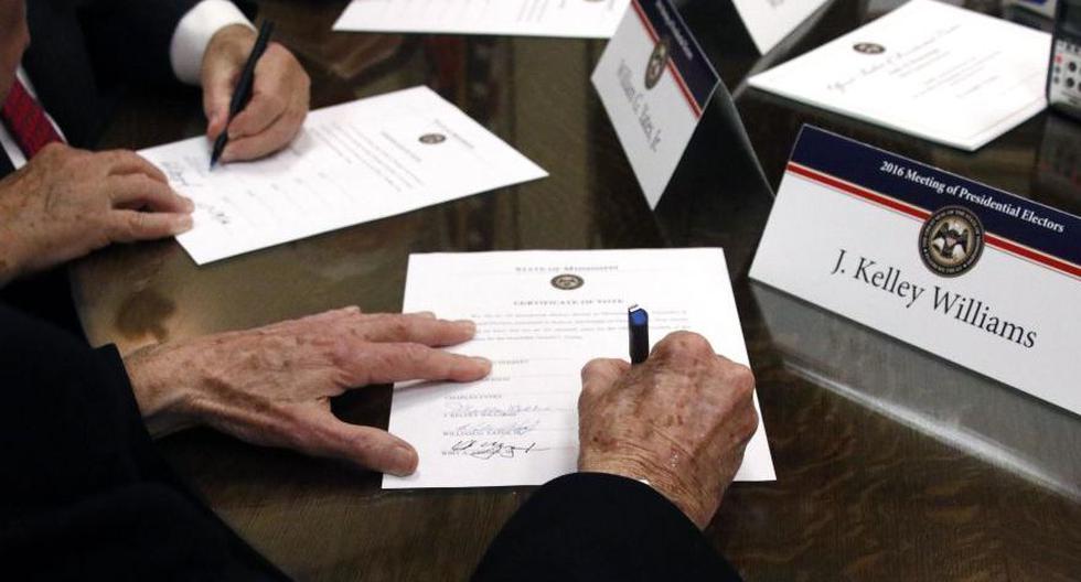 Los electores presidenciales se reúnen en todo Estados Unidos este lunes para elegir formalmente a Joe Biden como el próximo presidente de la nación. En la imagen, los miembros del Colegio Electoral de Mississippi firman certificados de voto de los comicios del 2016. (Foto: AP / Rogelio V. Solis)