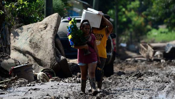 Personas portan pertenencias luego del paso del huracán Eta en el barrio Omonita en El Progreso, departamento de Yoro, Honduras, antes de la llegada del huracán Iota.  (Foto: AFP / Orlando SIERRA).