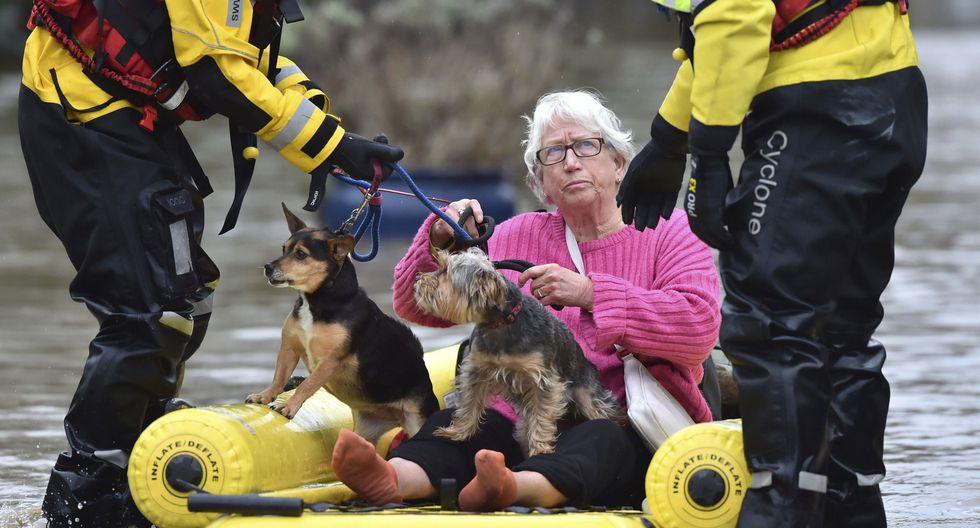 Equipos de rescate llevan a una mujer a un lugar seguro en Nantgarw, Gales. (Ben Birchall / PA vía AP).