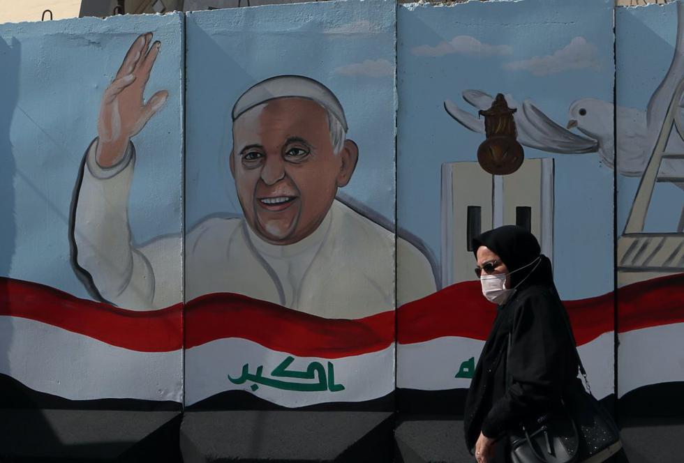 Una mujer pasa junto a un mural que representa al papa Francisco en un muro de concreto colocado por las fuerzas de seguridad iraquíes para rodear la Iglesia Nuestra Señora de la Salvación durante los preparativos para la visita del sumo pontífice a Bagdad, Irak. (AP/Khalid Mohammed).