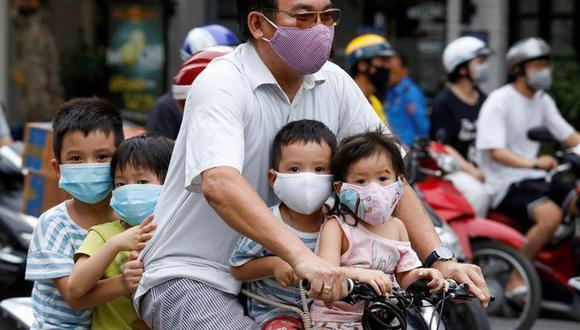 Coronavirus: Imagen de archivo de un hombre y sus hijos con mascarillas andando con bicicleta por Hanói, Vietnam, 27 julio 2020. (REUTERS/Kham).