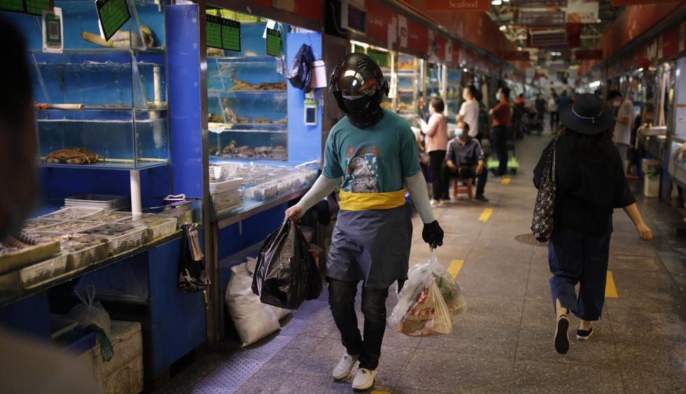 Personas con mascarillas por el coronavirus pasan por los puestos de mariscos en un mercado de Beijing (China). Autoridades continúan en alerta tras brote del COVID-19. (EFE/EPA/STRINGER).