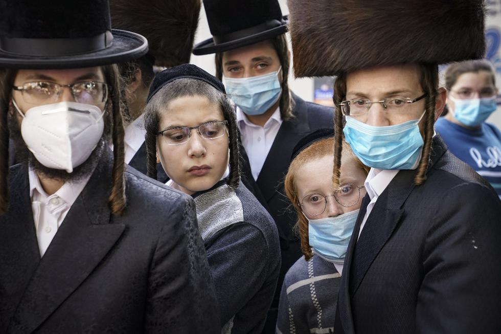 Miembros de la comunidad judía ortodoxa se reúnen alrededor de un periodista en medio de la pandemia del coronavirus en el vecindario de Borough Park del distrito de Brooklyn de Nueva York (Estados Unidos). (AP / John Minchillo).