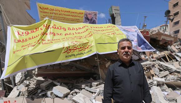 Samir Mansour, propietario de la librería y editorial del mismo nombre que tenía la colección más grande de literatura inglesa en Gaza, posa sobre los escombros de su negocio. (Foto de Emmanuel DUNAND / AFP).