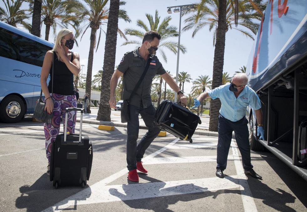 Los turistas alemanes se preparan para abordar un autobús a su llegada al aeropuerto de Son San Joan, en Palma de Mallorca, como parte de un programa piloto para reactivar el turismo en España. (JAIME REINA / AFP)