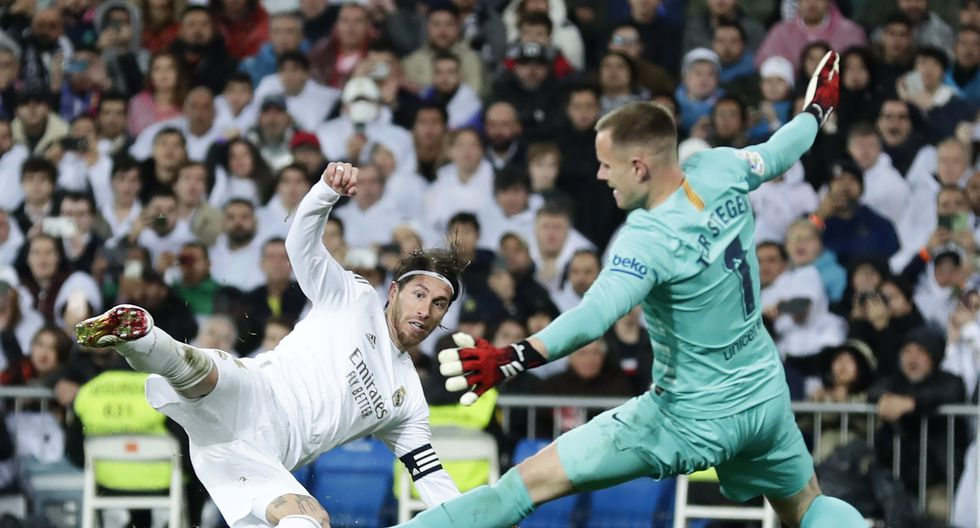 Barcelona's goalkeeper Marc-Andre ter Stegen, right, blocks a shot of Real Madrid's Sergio Ramos during the Spanish La Liga soccer match between Real Madrid and Barcelona at the Santiago Bernabeu stadium in Madrid, Spain, Sunday, March 1, 2020. (AP Photo/Manu Fernandez)