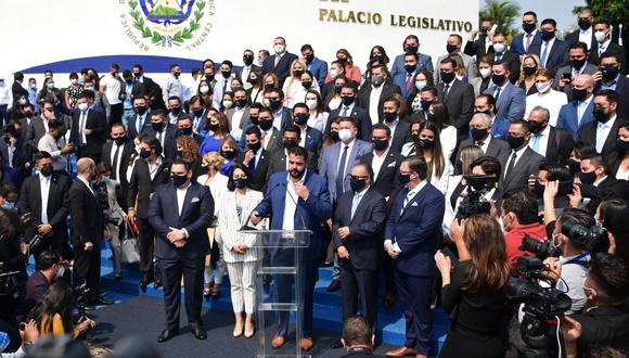 El presidente del partido gobernante de El Salvador Nuevas Ideas, Xavi Zablah (centro), primo del presidente Nayib Bukele, habla a los medios rodeado de los nuevos miembros de la Asamblea Legislativa. (Foto: Stanley ESTRADA / AFP).