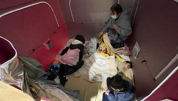 Una familia evacuada descansa en un refugio instalado en un estadio deportivo en Soma, prefectura de Fukushima, el 14 de febrero de 2021, después de que un terremoto de magnitud 7,3 sacudiera la costa este de Japón. (JIJI PRENSA / AFP).