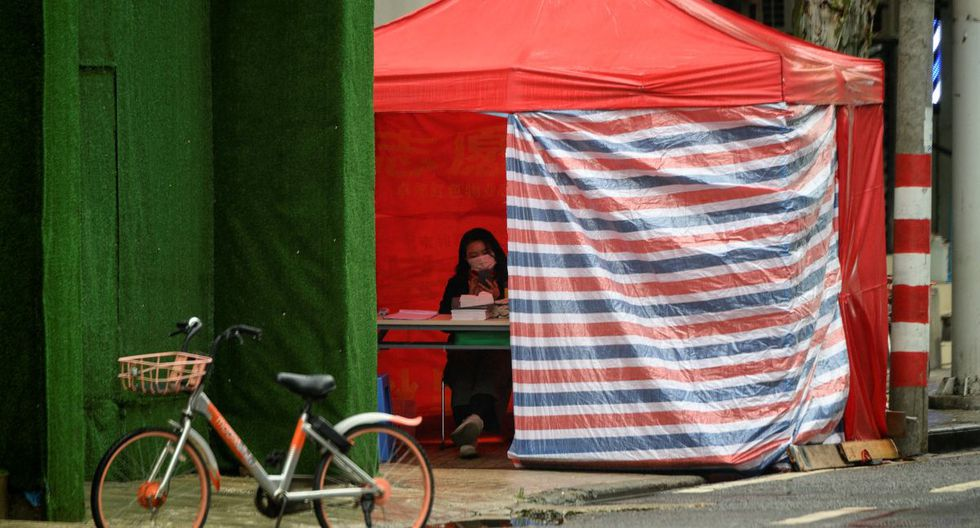 Un voluntario de la comunidad vigila la entrada de un complejo en Wuhan, en la provincia central china de Hubei. (Foto: AFP/Noel Celis)