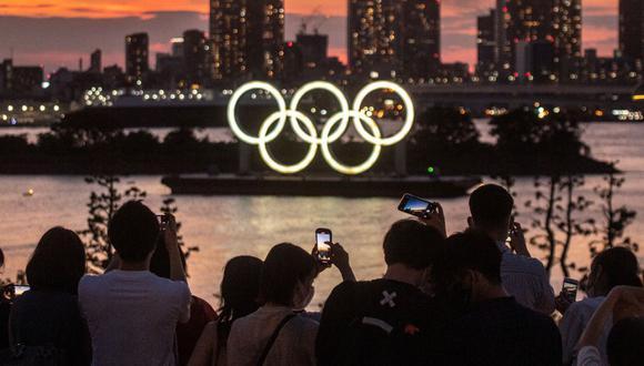 La gente toma fotografías mientras los anillos olímpicos se iluminan al anochecer en el paseo marítimo de Odaiba en Tokio, Japón, el 22 de julio de 2021. (Foto de Philip FONG / AFP).