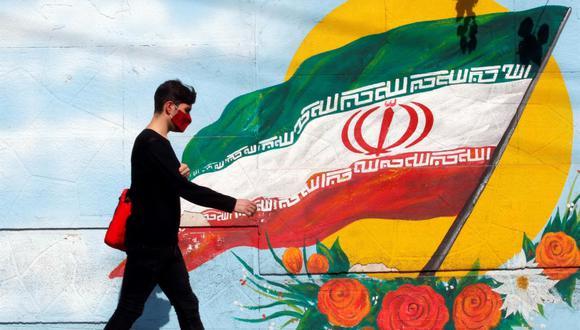 Un joven camina frente a un mural pintado con la bandera nacional de Irán. (EFE/ Abedin Taherkenareh).