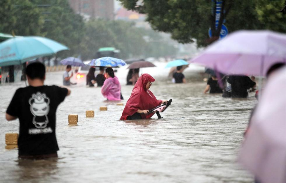 People walk on a flooded road after the rain that was recorded on Tuesday, July 20, 2021 in the central Chinese city of Zhengzhou in Henan Province.  (EFE / EPA / FEATURECHINA CHINA).