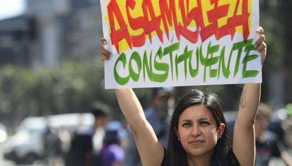 """Una mujer sostiene un letrero que dice """"Asamblea Constituyente"""" mientras la gente se manifiesta en Santiago de Chile el 24 de octubre de 2019. (Foto de Martin BERNETTI / AFP)."""