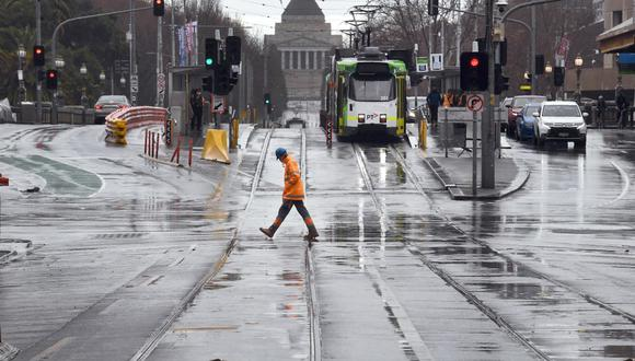 Un trabajador cruza la calle en el distrito comercial central de Melbourne, mientras la ciudad lucha contra un brote del coronavirus. (William WEST / AFP)