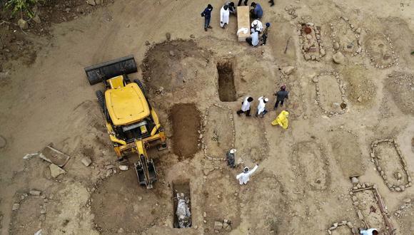 En esta fotografía aérea tomada el 16 de abril de 2021, familiares y amigos se reúnen para enterrar los cadáveres de las víctimas del coronavirus Covid-19 en un cementerio de Nueva Delhi, India. (Foto de Archana THIYAGARAJAN / AFP).