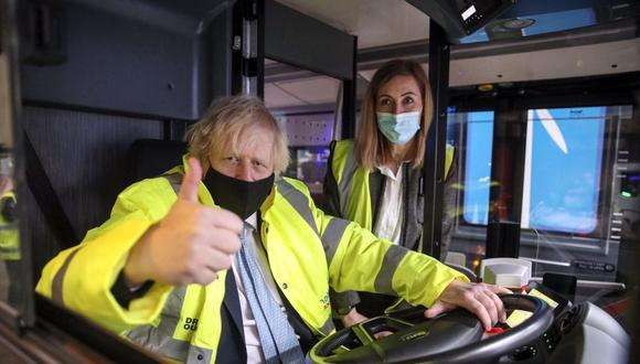 El primer ministro británico, Boris Johnson, levanta el pulgar mientras se sienta en el asiento del conductor de un autobús eléctrico. (Foto de Steve Parsons / POOL / AFP).