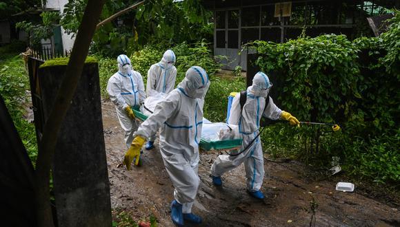 Voluntarios con equipo de protección personal (EPP) llevan el cuerpo de una víctima del coronavirus Covid-19 a un cementerio en Myanmar. (Foto de Ye Aung THU / AFP).