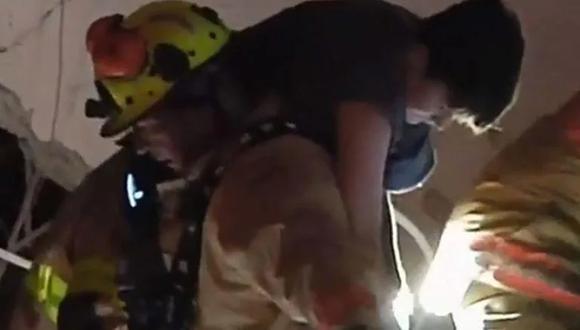 Los bomberos rescatan a un niño de entre los escombros del edificio Champlain Towers en Miami. (Captura de video).