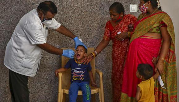 Un trabajador sanitario toma una muestra a un niño para una prueba de detección del coronavirus en Hyderabad, India, el 29 de abril de 2021. (AP Foto/Mahesh Kumar A.).