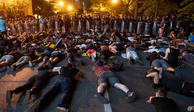 Los manifestantes en el suelo frente a una línea de policía frente a la Casa Blanca durante las protestas por la muerte de George Floyd en Washington. (Foto: AFP / ROBERTO SCHMIDT).
