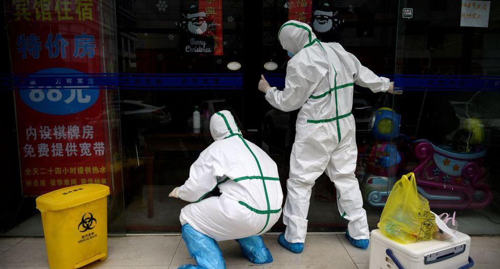 Los trabajadores médicos, que usan trajes de materiales peligrosos, cierran una puerta de una clínica de pruebas para el nuevo coronavirus en Wuhan, en la provincia central de Hubei de China. (Foto: AFP/Noel Celis)