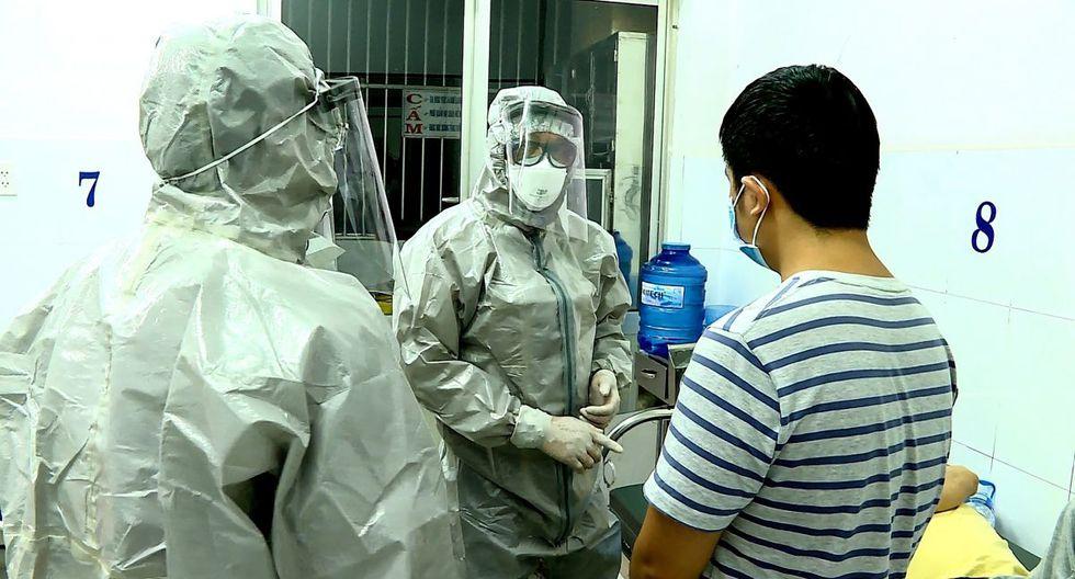 Personal médico usa trajes de protección para interactuar con dos pacientes que dieron positivo al coronavirus. Ellos están en una sala de aislamiento en el hospital Cho Ray en la ciudad de Ho Chi Minh en Vietnam (Foto: AFP)