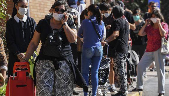 La gente hace cola para comprar en un supermercado en Santiago, Chile. (Foto: Martin Bernetti / AFP)