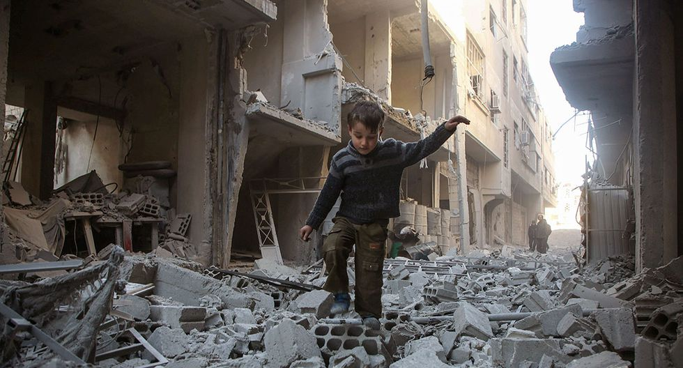TOPSHOT - A Syrian boy walks through a street covered with rubble from a heavily damaged building following air strikes by regime forces in Arbin, in the rebel-held Eastern Ghouta region on the outskirts of the Syrian capital Damascus, on February 1, 2018. Arbin is in the Eastern Ghouta region which has been under government siege since 2013. / AFP / Amer ALMOHIBANY