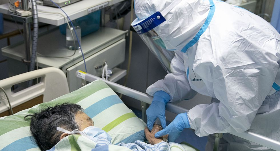 Una enfermera sostiene la mano del paciente para consolarlo mientras está en la Unidad de cuidados intensivos (UCI). (Foto: AFP)