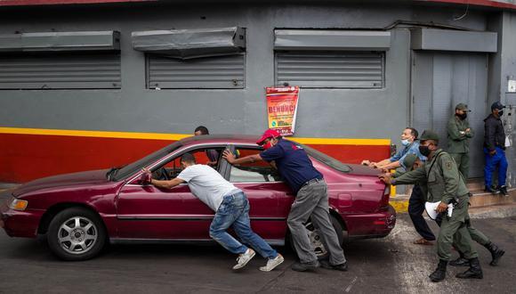 Un grupo de civiles y militares empujan un vehículo que se quedó sin gasolina en Caracas (Venezuela). (EFE/ Miguel Gutiérrez).