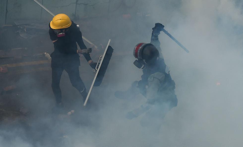 Un manifestante es golpeado por la policía antidisturbios mientras intentaba encontrar una salida segura del campus de la Universidad Politécnica de Hong Kong. (Foto por Ye Aung Thu / AFP).