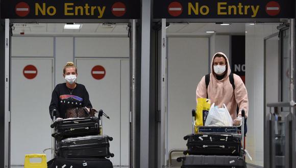 En esta foto del 8 de junio, pasajeros con equipo de protección personal, incluyendo una máscara facial como medida de precaución contra el coronavirus COVID-19, llegan a la Terminal 1 del aeropuerto de Manchester, en el noroeste de Inglaterra. (Foto: AFP / Oli Scarff)