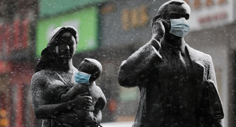 Estatuas con mascarillas faciales en medio de la nieve en Wuhan, el epicentro del nuevo brote de coronavirus. (Reuters).