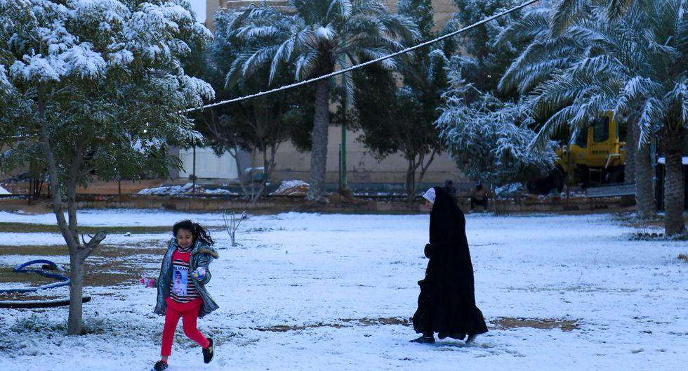 Una niña iraquí juega con su madre en la nieve en la ciudad sagrada chiíta de Kerbala. (AFP)