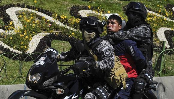 La policía antidisturbios arresta a un hombre durante la procesión fúnebre de ocho partidarios del expresidente boliviano Evo Morales, asesinado cuando las fuerzas de seguridad levantaron un asedio a una planta de combustible, en La Paz, el 21 de noviembre. (Foto: Archivo/AFP).