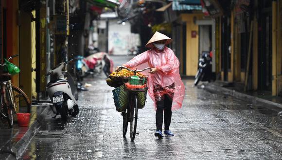 Una vendedora de frutas que usa una máscara facial camina por una calle en Hanoi. Hasta el momento Vietnam no registra ninguna muerte por coronavirus (Foto: Nhac NGUYEN / AFP).