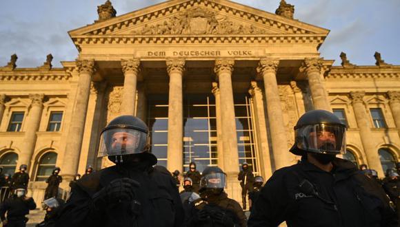 Policías montan guardia frente al edificio del Reichstag el sábado, cuando un grupo de manifestantes que se oponen al uso de las mascarillas contra el coronavirus intentaron entrar al edificio. (Foto de John MACDOUGALL / AFP).