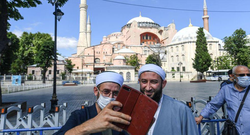 Dos hombres se tomaron una selfie frente a Santa Sofía el 11 de julio de 2020 en Estambul, un día después de que un tribunal turco decidiera que sea convertida en mezquita. (Foto por Ozan KOSE / AFP).
