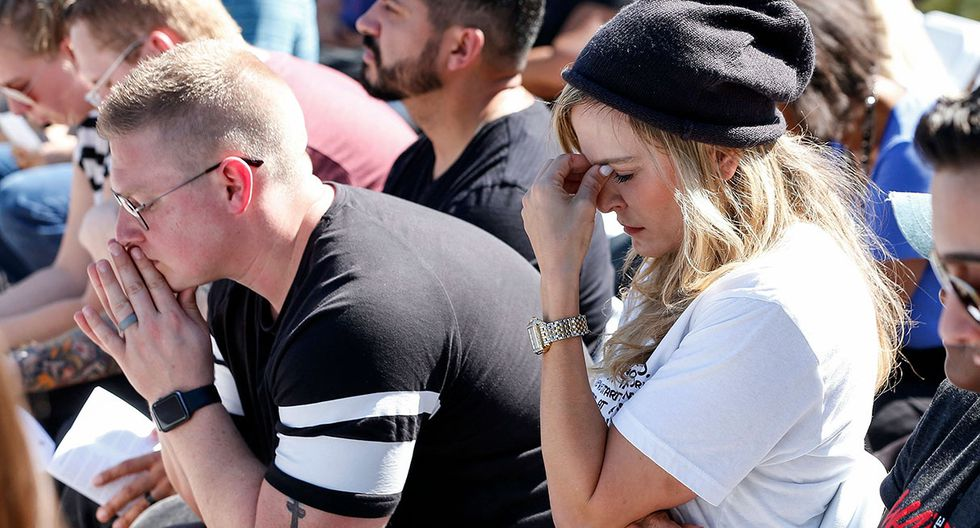 Mourners react during a prayer vigil for the victims of the Marjory Stoneman Douglas High School shooting at Parkridge Church in Coral Springs, Florida on February 15, 2018.  The heavily armed teenager who gunned down students and adults at a Florida high school was charged Thursday with 17 counts of premeditated murder, court documents showed.Nikolas Cruz, 19, killed fifteen people in a hail of gunfire at Marjory Stoneman Douglas High School in Parkland, Florida. Two others died of their wounds later in hospital, the sheriff's office said.  / AFP / RHONA WISE