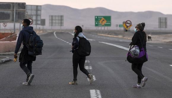 Los migrantes venezolanos Reinaldo (izquierda), Anyier (derecha) y su hija Danyierly, 14, caminan por la carretera camino a Iquique, luego de cruzar desde Bolivia, el 18 de febrero de 2021. (Foto de MARTIN BERNETTI / AFP).